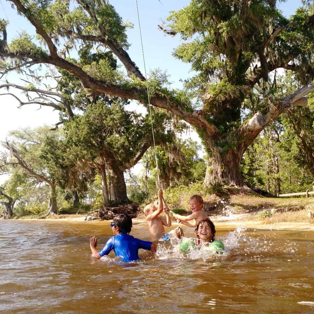 4 children play on a rope swing in the waters of Black Water Bay in the Florida Panhandle.