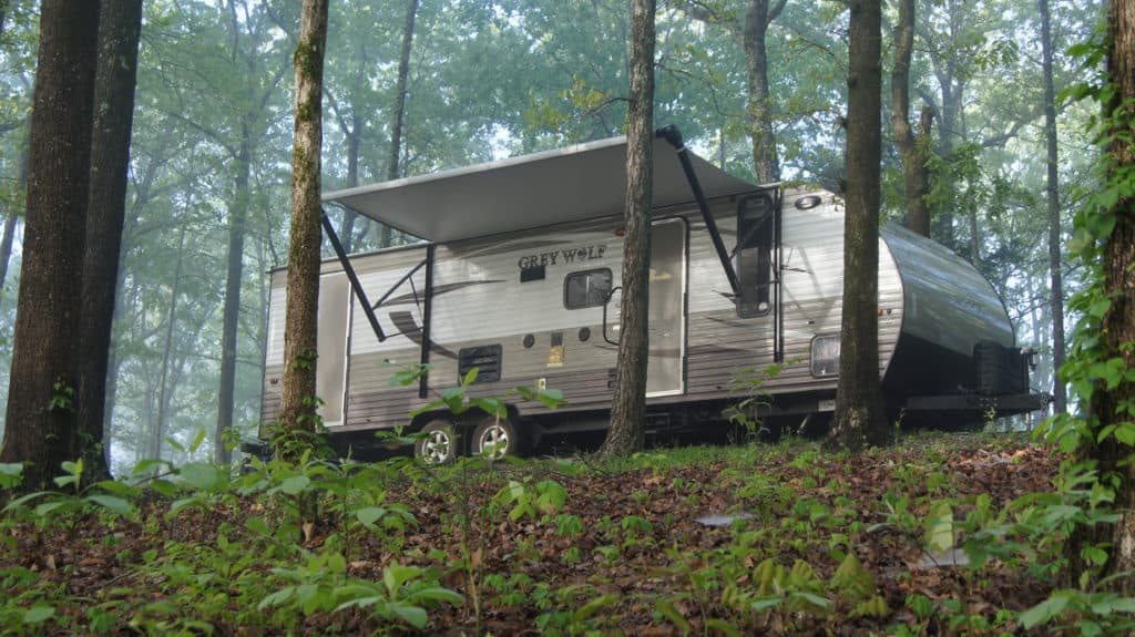 A travel trailer in the woods at Meriwether Lewis Monument Campground in Tennessee.