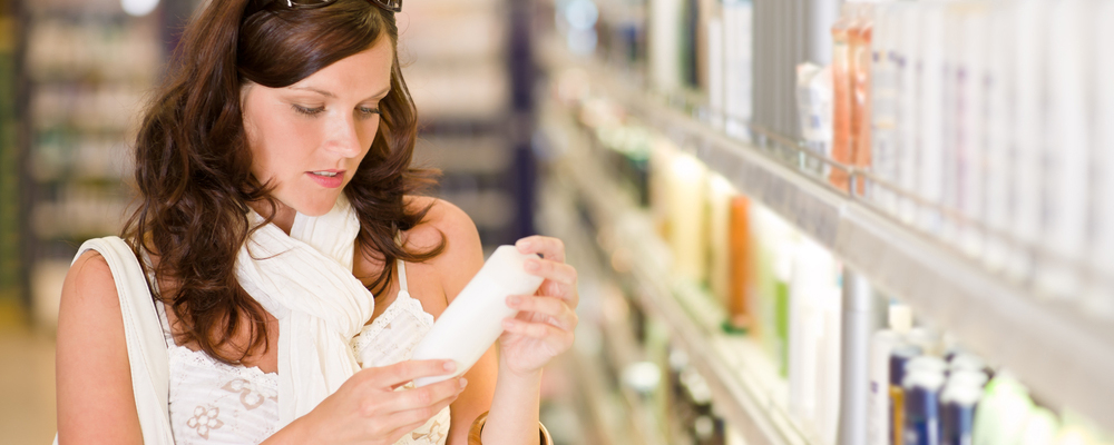 Shopping - young woman holding bottle of shampoo in supermarket