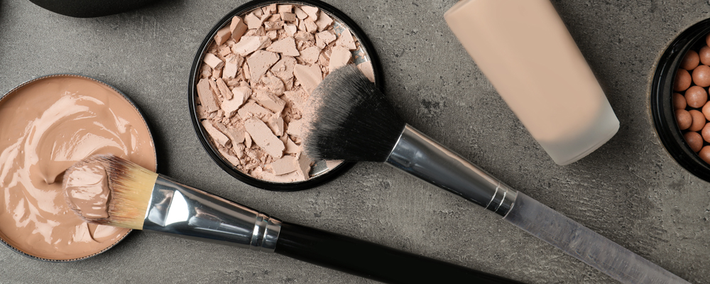 Flat lay composition with skin foundation, powder and beauty accessories on grey background