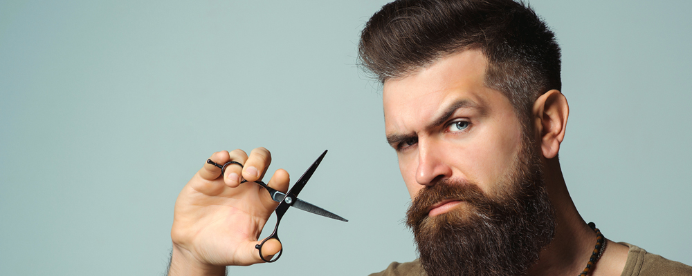 Stylish bearded man. Barber holding scissors. Small business, barber shop. Handsome hairstylist. Mens haircut, beard care. Male bearded style, fashion. Barber professional tools. Vintage barbershop.