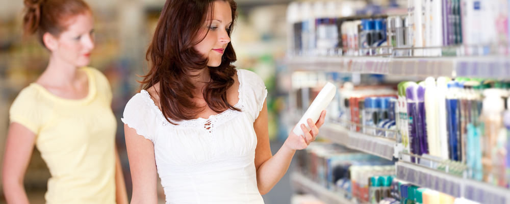 Woman holding bottle of shampoo in cosmetics department