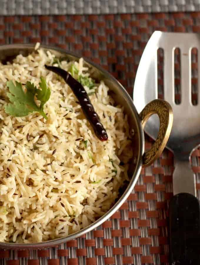 Jeera Rice on a deep vessel garnish with some cilantro on a dark colour mat |