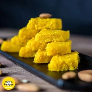 Nariyal ki barfi on a black plate with some almonds and pictachios