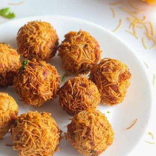 Paneer Vermicelli Balls on a white plate with some sev sprinklers garnished with some coriander leaves