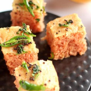 Suji Dhokla on a black plate tempered with a white background and some tomato sauce on a yellow small bowl