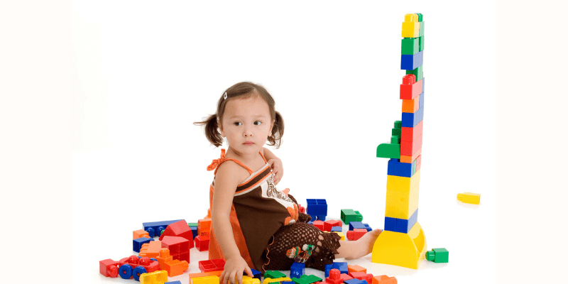 Young girl playing with building blocks