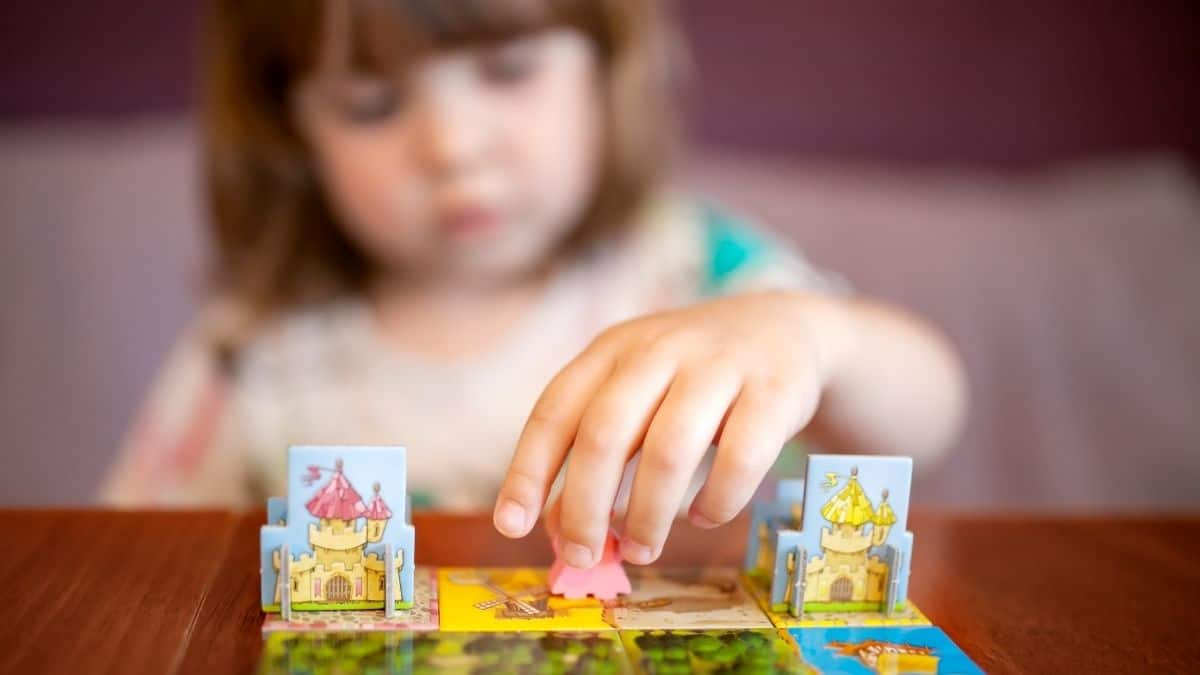 Young girl playing with a colorful board game