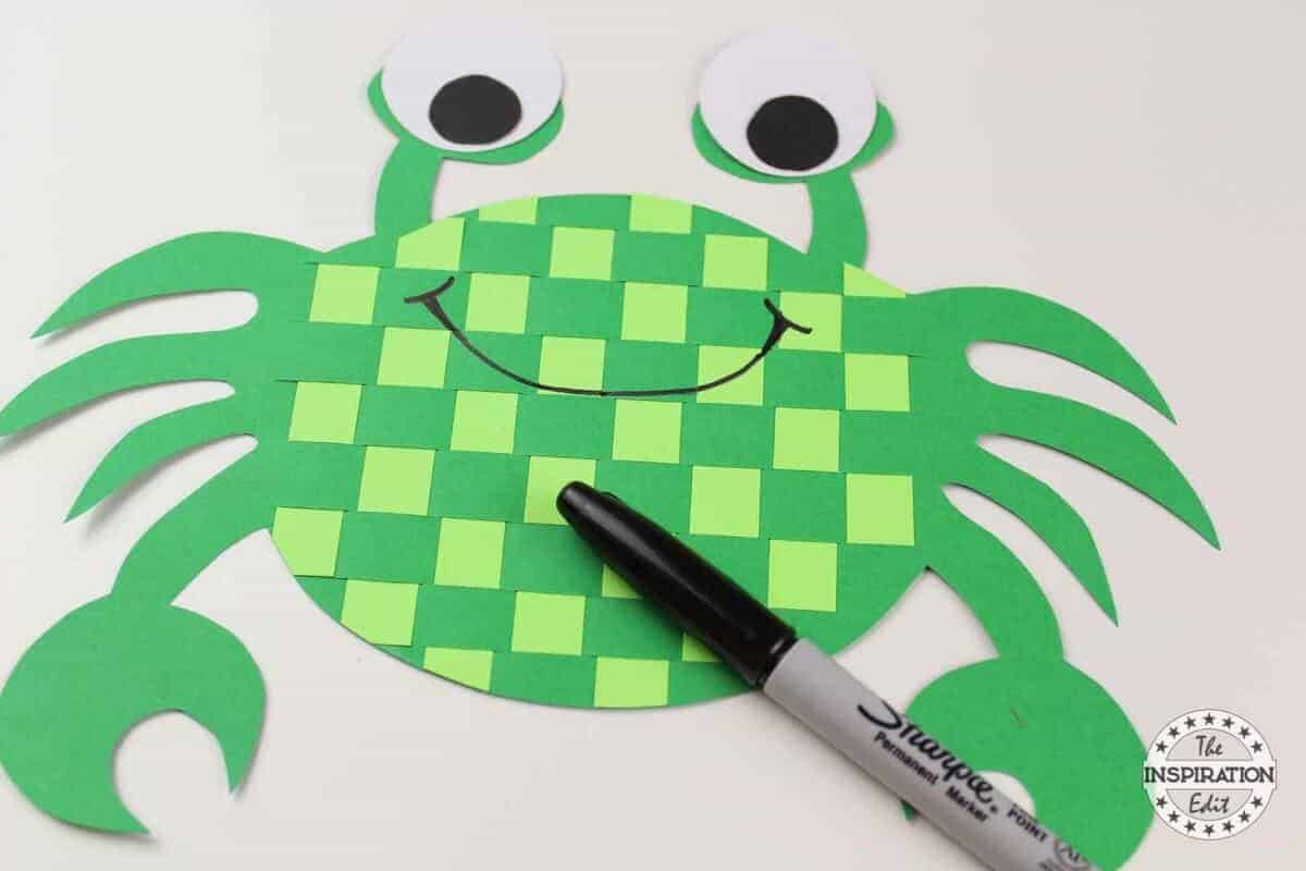 drawing a smile on the face of the crab craft with a black pen