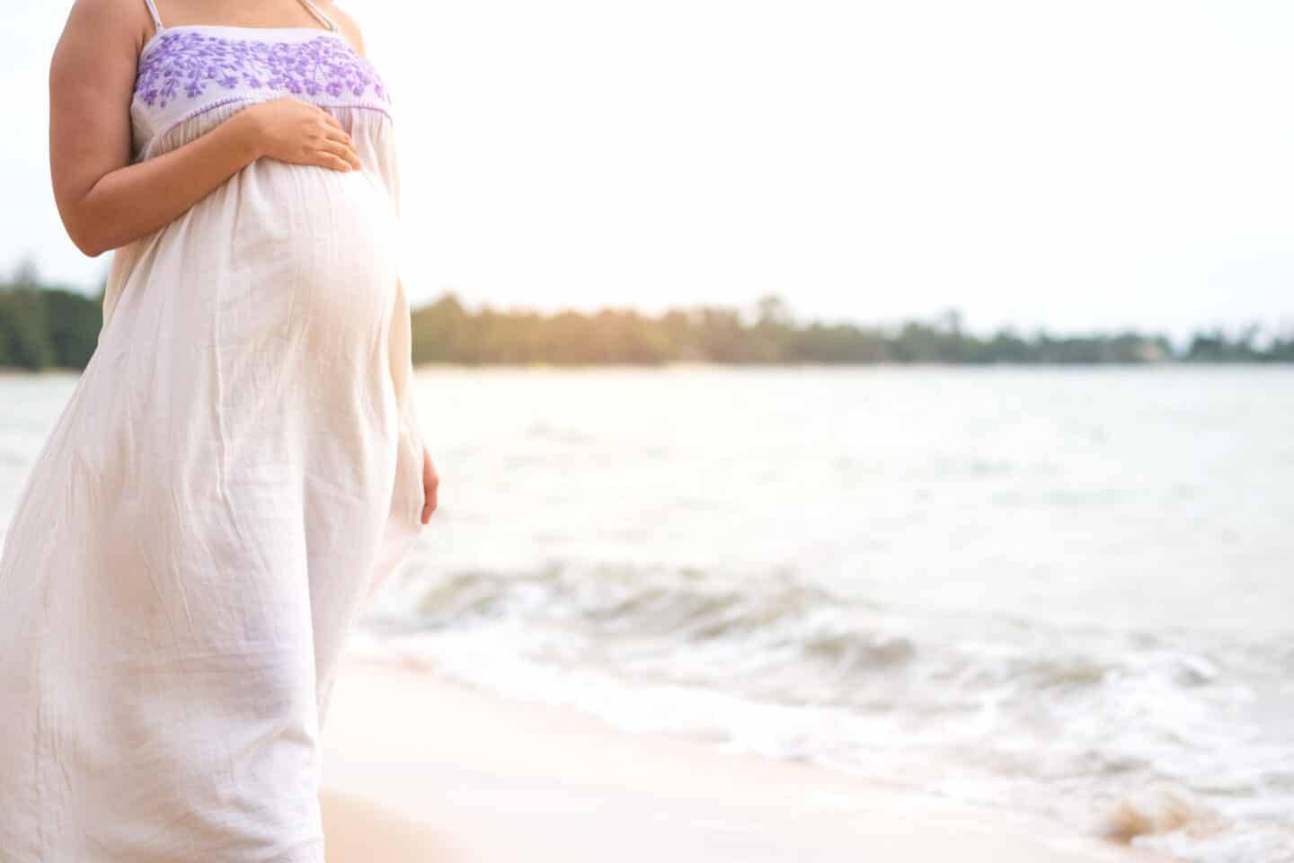 Pregnant woman standing on beach hand touching on her belly.