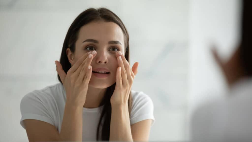 Close up smiling young woman wearing white t-shirt doing facial massage