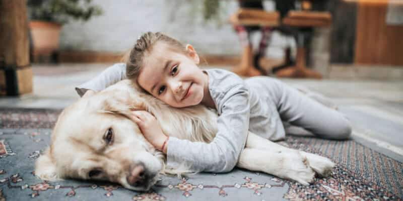 Cute little girl relaxing with her dog on carpet at home