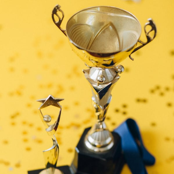 Two golden trophies on a yellow background