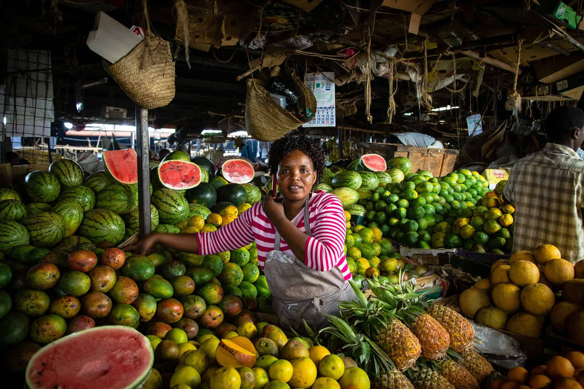 Woman among fruits in a food market in Nairobi