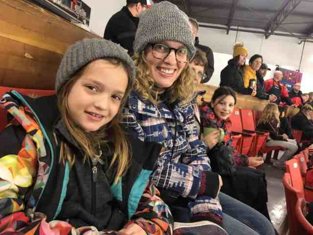 Spectators watching a hockey game dressed warmly with winter jackets, gloves and ski hats