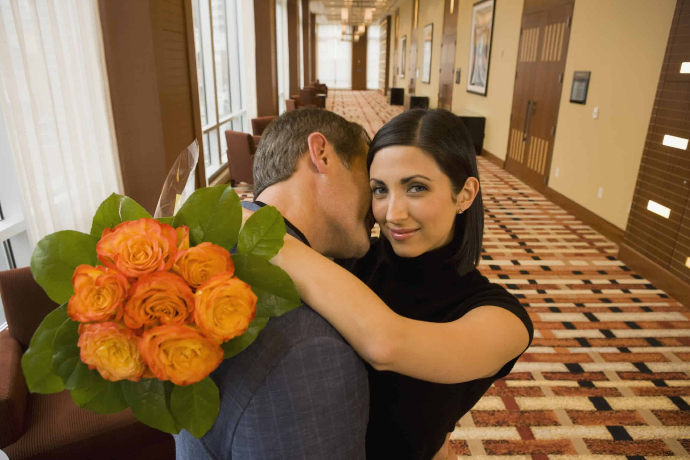 couple kissing, couple canoodling, couple making out, couple in hotel, man and woman in hotel, man and woman with flowers