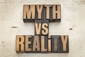 Wooden tiles spelling out the phrase myth vs reality in referrence to fitness myths and facts