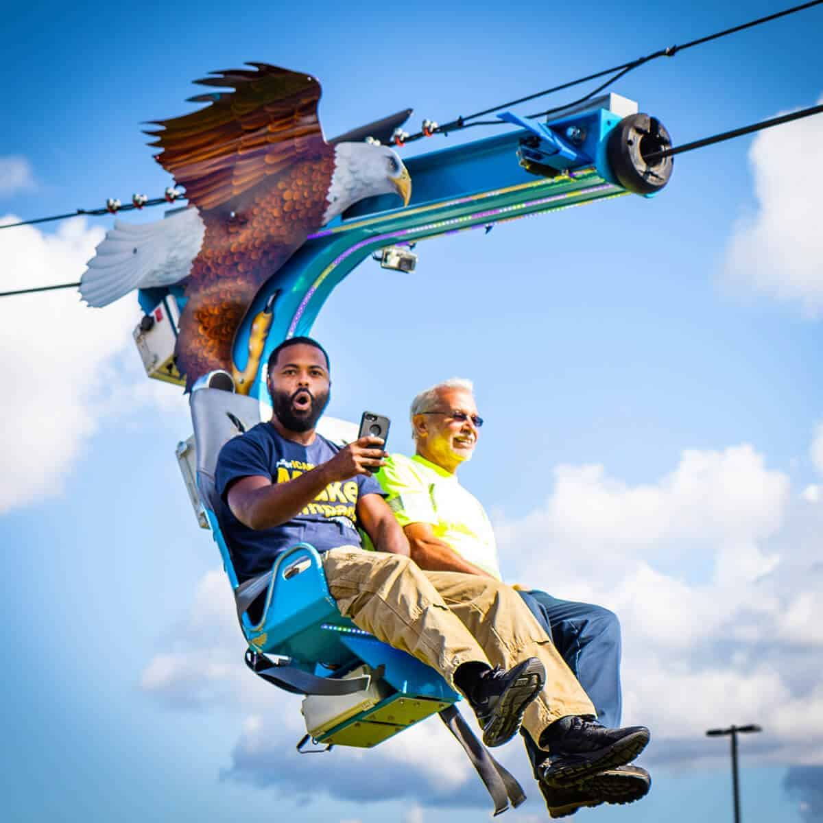 Men from corporate party enjoying themselves on the Soaring Eagle zip line