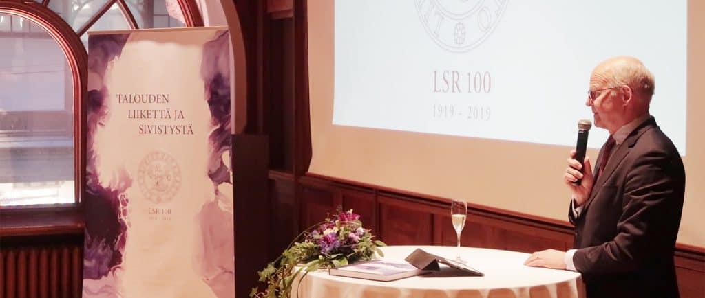LSR:n hallituksen puheejohtaja Reijo Karhinen avasi historiikin julkistustilaisuuden.
