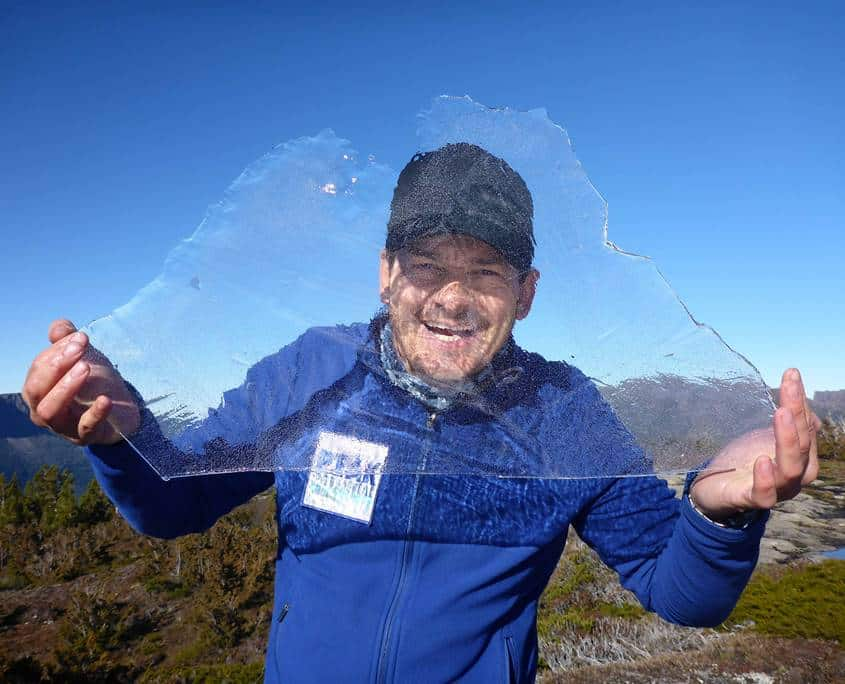 Shane Pophfer hold up a sheet of ice on our Tasmanian Adventure through the Overland Track