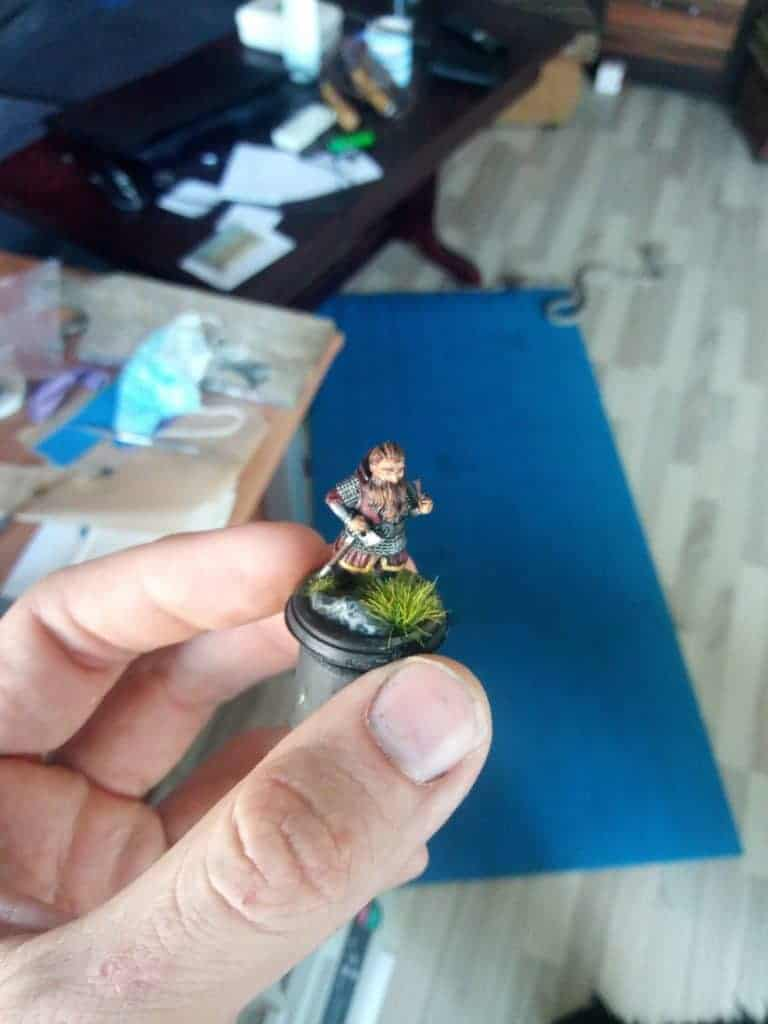 A hand keeping a painted 3d miniature of a dwarf standing on the grass