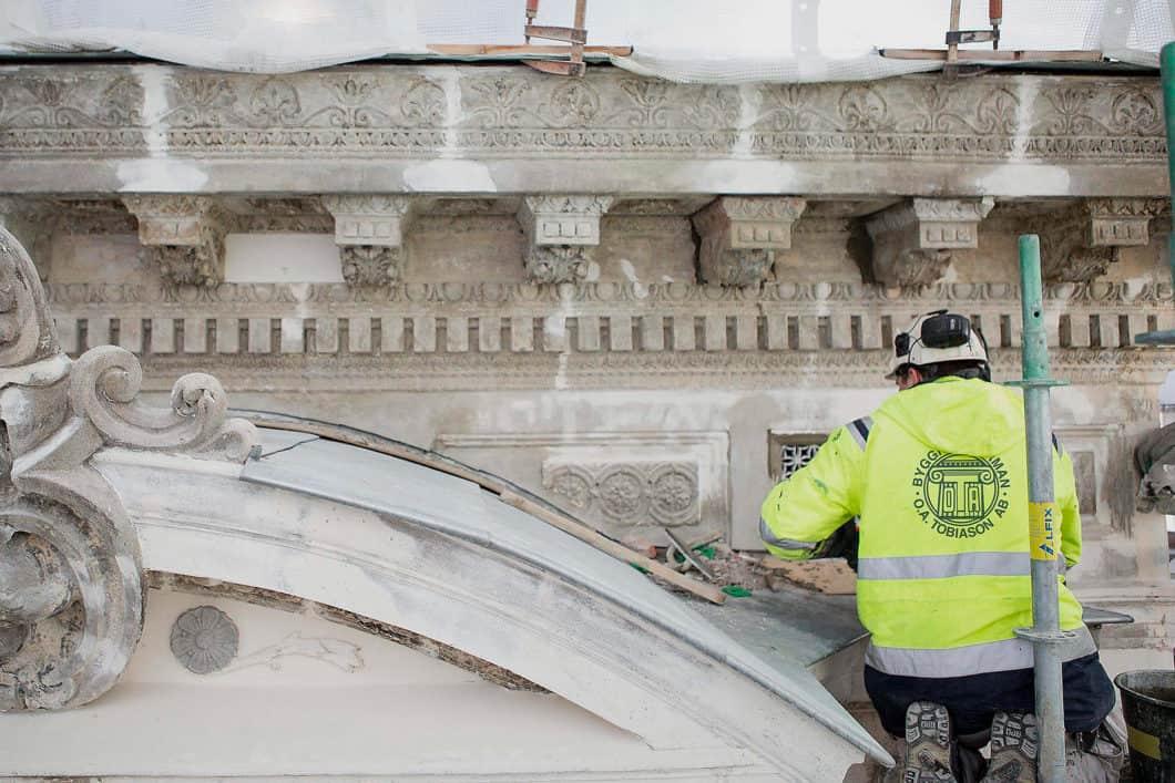 Person i O.A. Tobiason-jacka som arbetar på fasad.