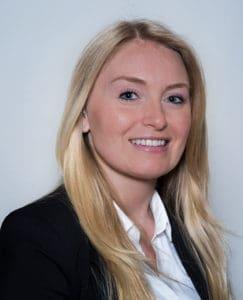 Bild einer jüngeren lächelnden Dame mit blonden Haaren und weißem Hemd