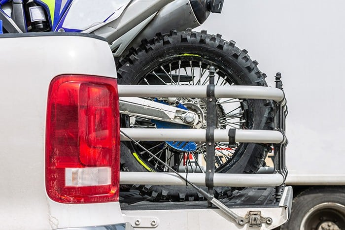 Rear viwe truck bed extender with two dirt bike motorcycles on the back of the truck with safety gear in residential setting
