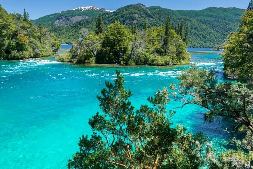 Crystal clear turquoise water in a lake surrounded by bright green trees