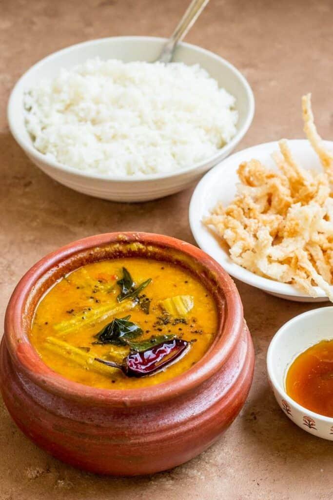 Instant Pot Sambar Recipe in a clay pot served with fryums and rice, Authentic Drumstick Sambar, Murungakka Sambar
