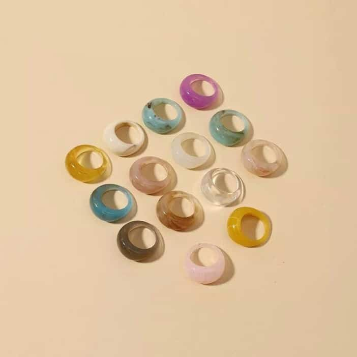 collection of Retro Colourful Resin Rings in multiple colours on yellow background