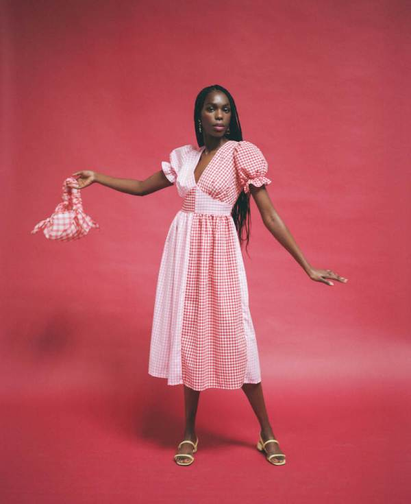 black woman wears tilda dress in red and pink gingham from Molby the label, gingham red bag and green strappy shoes.