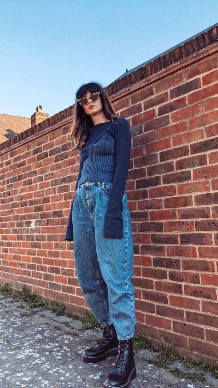 Founder and editor of Wear Next Daisy Jordan wears Fanfare Label navy jumper with bodice, slouchy denim jeans, chunky boots and a pair of tortoiseshell sunglasses as she stands in front of a red brick wall