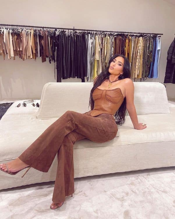 Kim Kardashian wearing a brown leather corset and suede trousers
