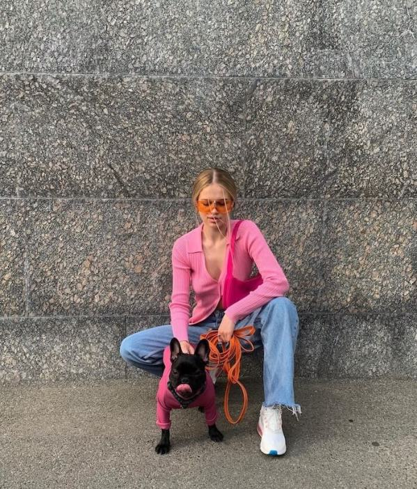 Woman wears asos pink top, jeans, trainers and sunglasses
