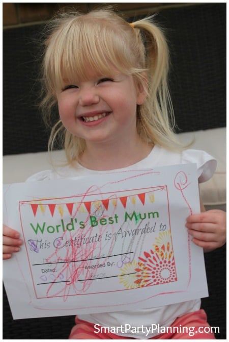 Child holding up the Mother's Day Certificate