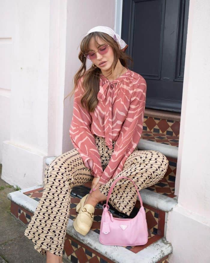 Influencer Sara Waiste sits on a doorstep wearing a babushka scarf, pink sunglasses, a tiger pussybow blouse in pink, cream trousers with wavy black lines, yellow loafers with a pink Prada nylon big sitting beside her.