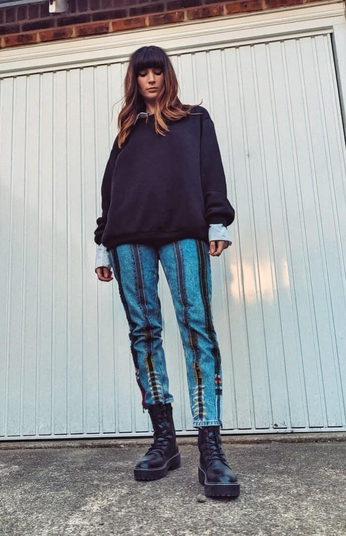 Founder and editor of Wear Next Daisy Jordan wears Fanfare Label upcycled jeans with chunky black boots and an oversized black sweatshirt, standing in front of a white garage door.