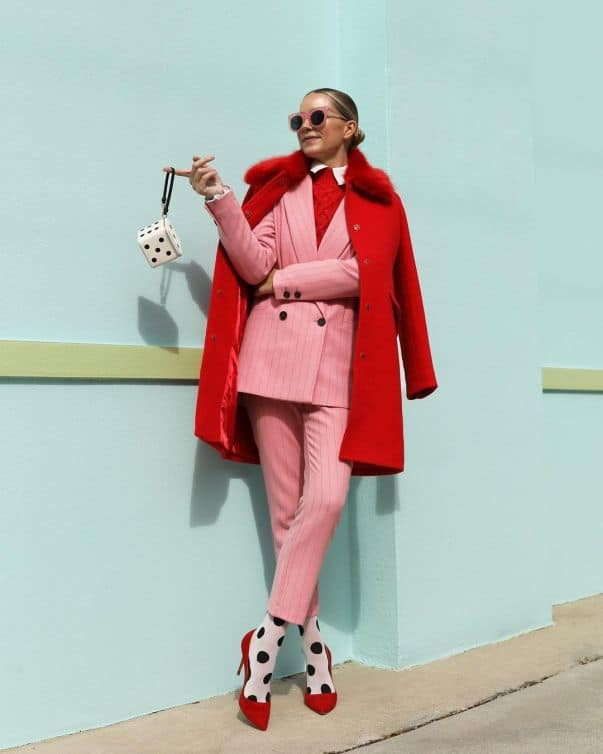 blaireadiebee wearing a pastel pink striped trouser suit with a red coat, heels, jumper and polka dot tights.