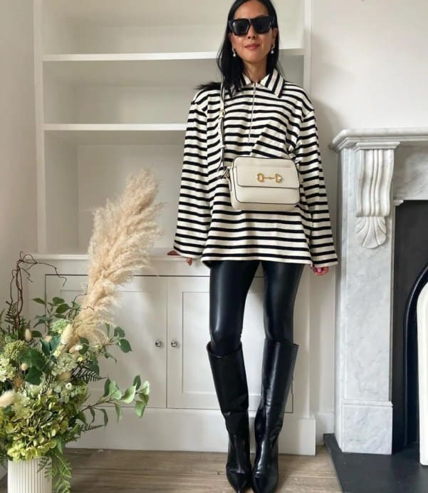 Debbie Le from @theFashionablePan wearing a striped top, leather look leggings and knee-high stomper boots