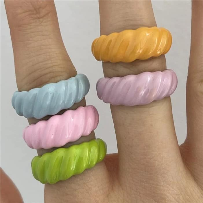 Hand wearing 5 Spiral Polymer Clay Rings in multi colours