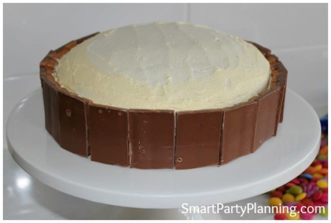 Place Kit Kat fingers around the base of the cake