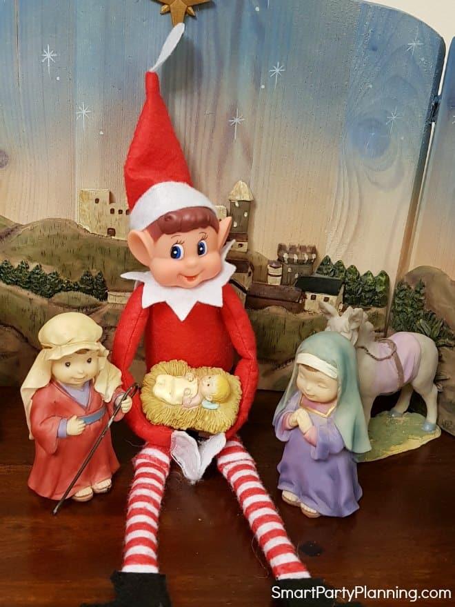 Elf on the Shelf holding baby Jesus