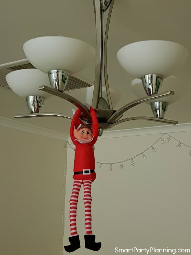 Elf on the shelf hanging from the light