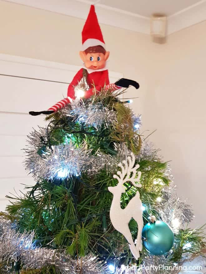 Elf on the shelf sitting on the top of a Christmas tree