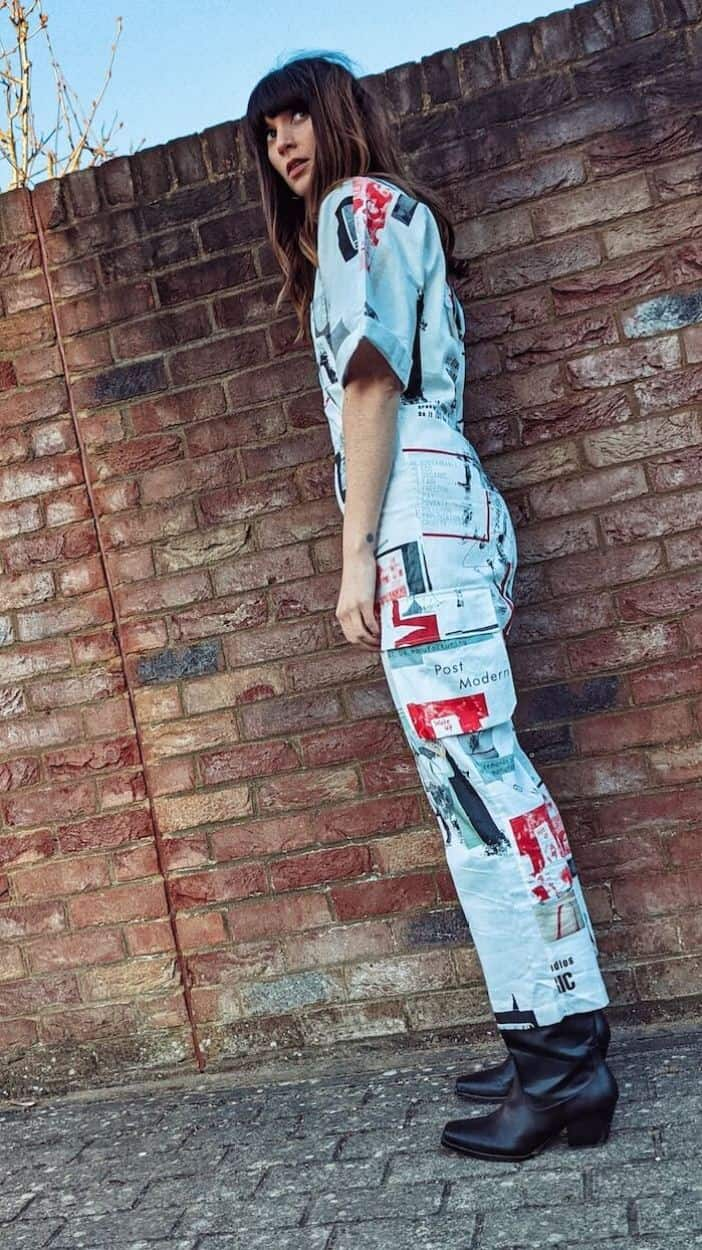 Founder and editor of Wear Next Daisy Jordan wears Fanfare Label printed white boilersuit and black western boots as she stands in front of a red brick wall