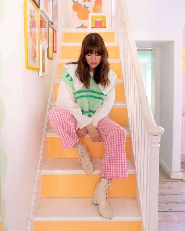 Lindsey Isla wearing pink gingham trousers and a clashing printed sweater vest.