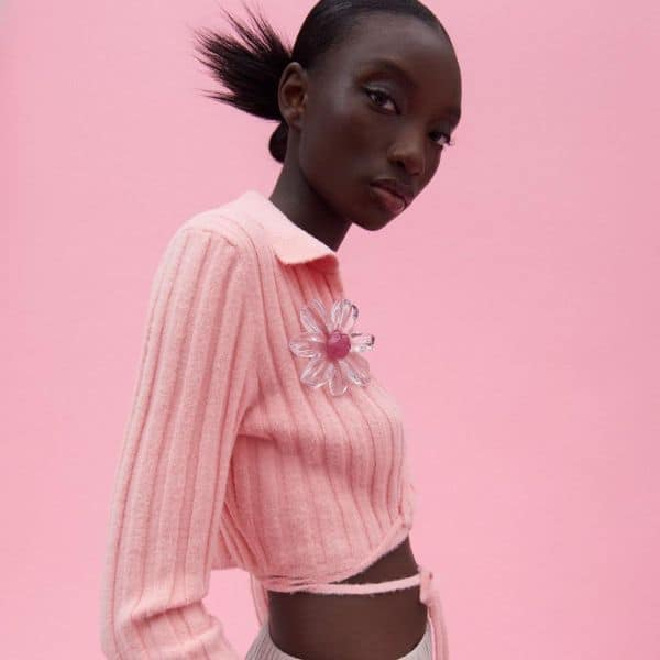 Zara model wears pink cardigan with large floral plastic broche.