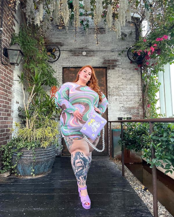 Plus-size model Tess Holliday wears wavy mesh mini dress, a lilac fluffy bag and lilac strappy heels