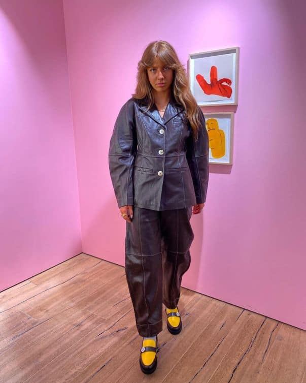 Laura Elizabeth Klein wearing a leather blazer and trousers from GANNI